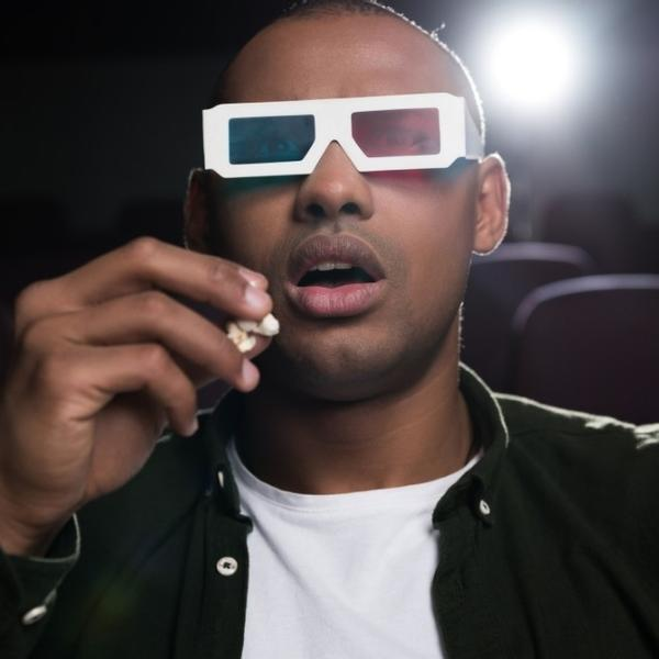 A young man watching a movie in the cinema.