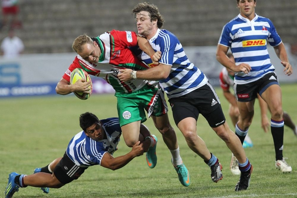 Four Rugby players are fighting on the ball during a rugby game.