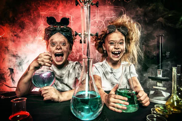 Funny school children doing science experiments in the laboratory.