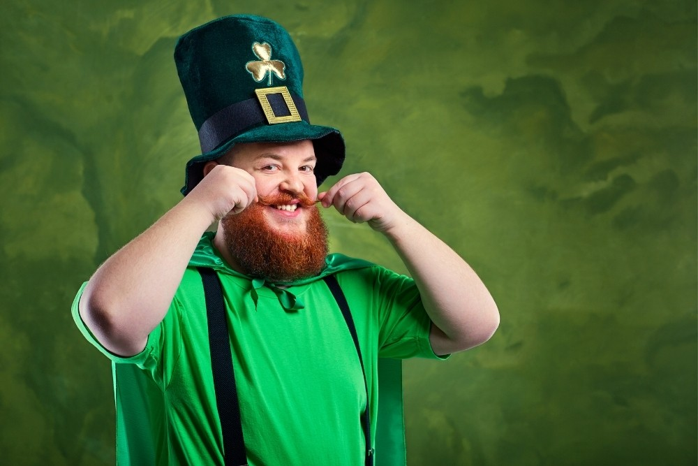 A smiling red-bearded man dressed in green for St. Patrick holding his mustache.