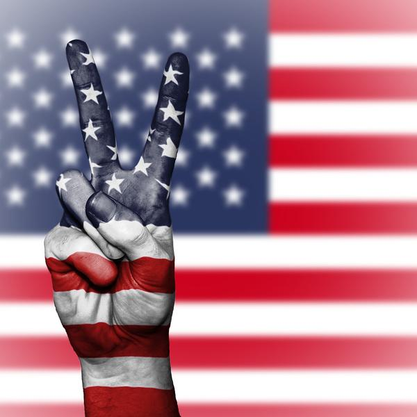 US flag with a hand making the peace sign.