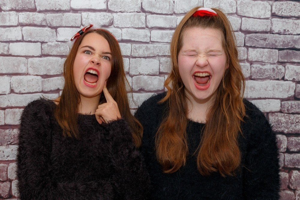 Two teenage girls doing funny faces.