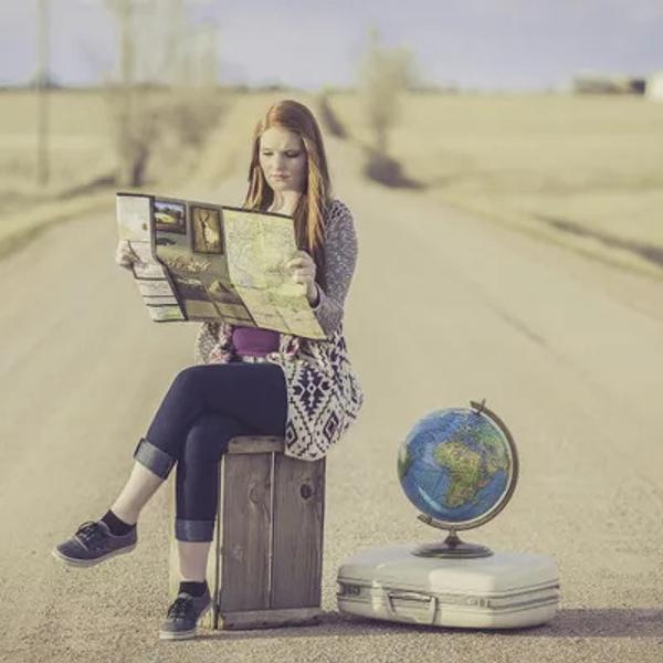 Woman traveler sitting on luggage with a map and globes.