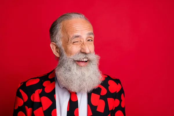 A funny old man wearing a suit with a heart for Valentine's Day.
