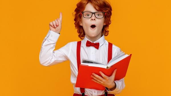 A cute kid with educational books, glasses, raising his finger in the air after he learned something.