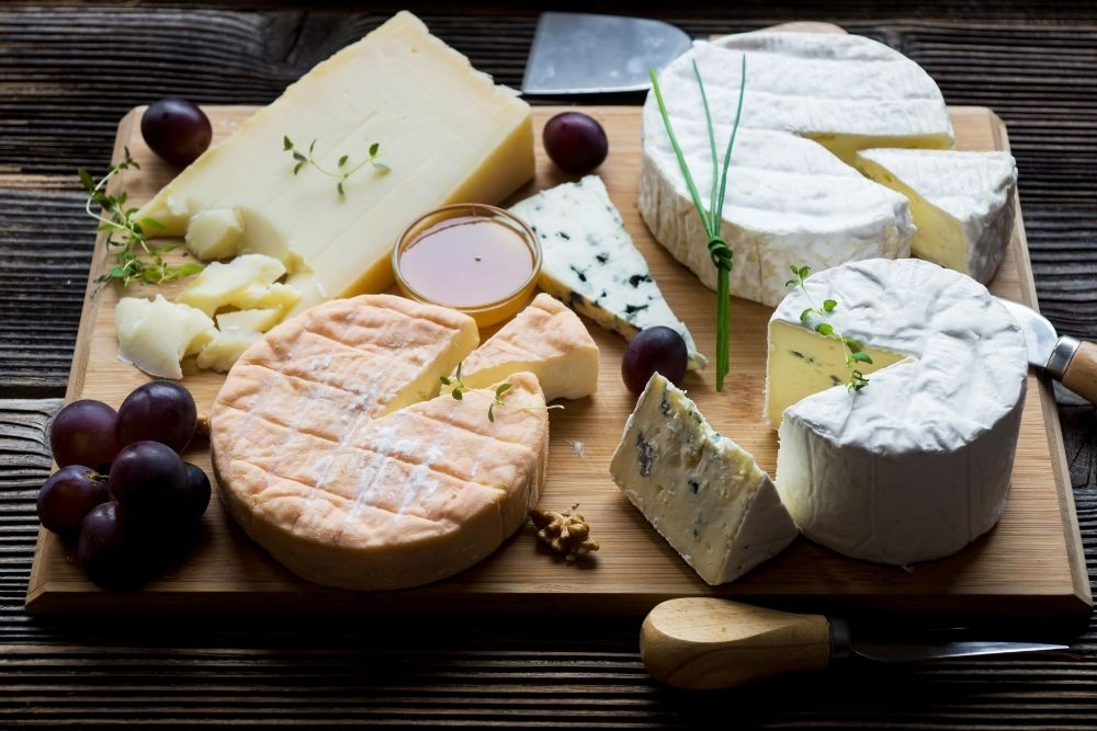 Few types of CHeese on a wooden desk.