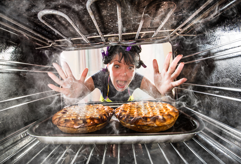 A funny woman looking at her burned food.