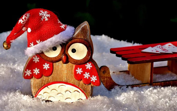 Funny Christmas owl doll with Christmas hat on a snowy background.