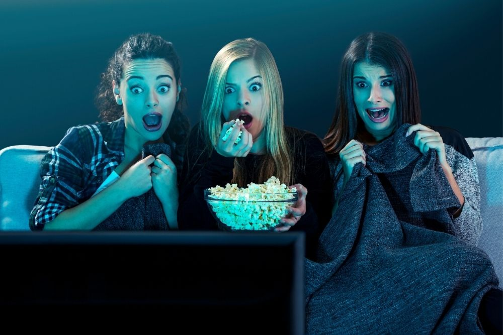 Three young girls sitting on a sofa and watching a movie with popcorn.