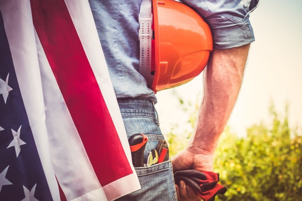 A Labor man with labor tools and an American flag.