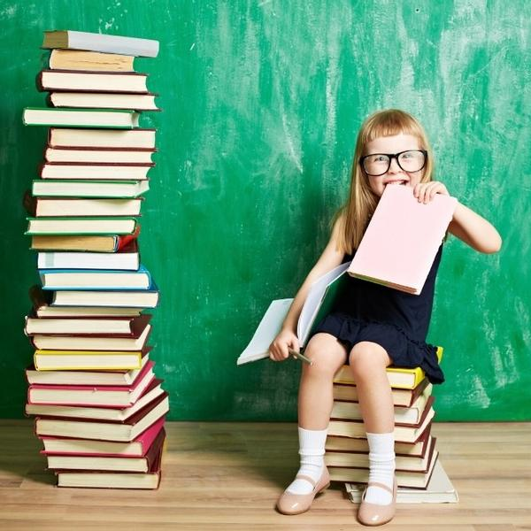 A funny girls reading literature, with many books around her.