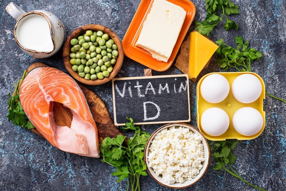 Food rich with Vitamin D & nutrients, and The words vitamin D are written on a chalkboard.