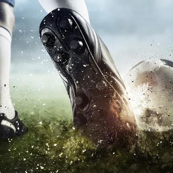 Soccer player kicking the ball closeup.