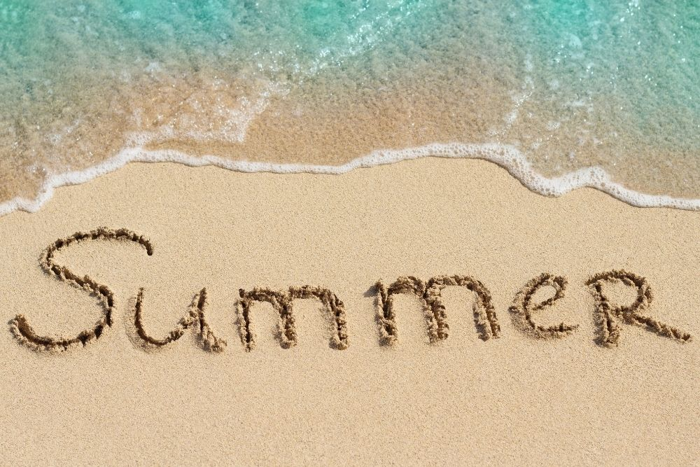 The word summer is written on the sand on the beach.