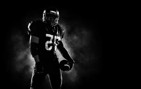 NFL Football player holding a Football ball on a black background.