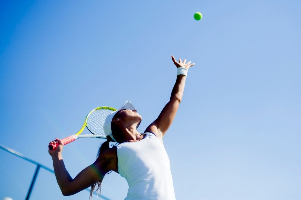 A woman playing tennis is serving the ball.