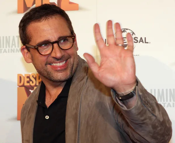Steve Carell saying hi with his hand.