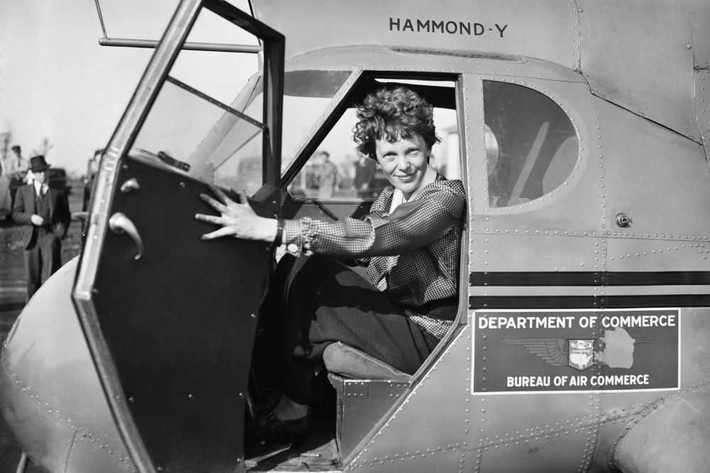 Amelia Earhart getting out of her plane. She is part of Women's history.