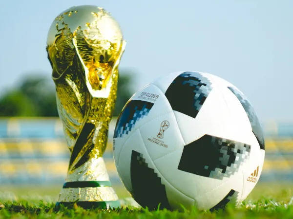 World Cup trophy and a soccer ball on a soccer court grass.
