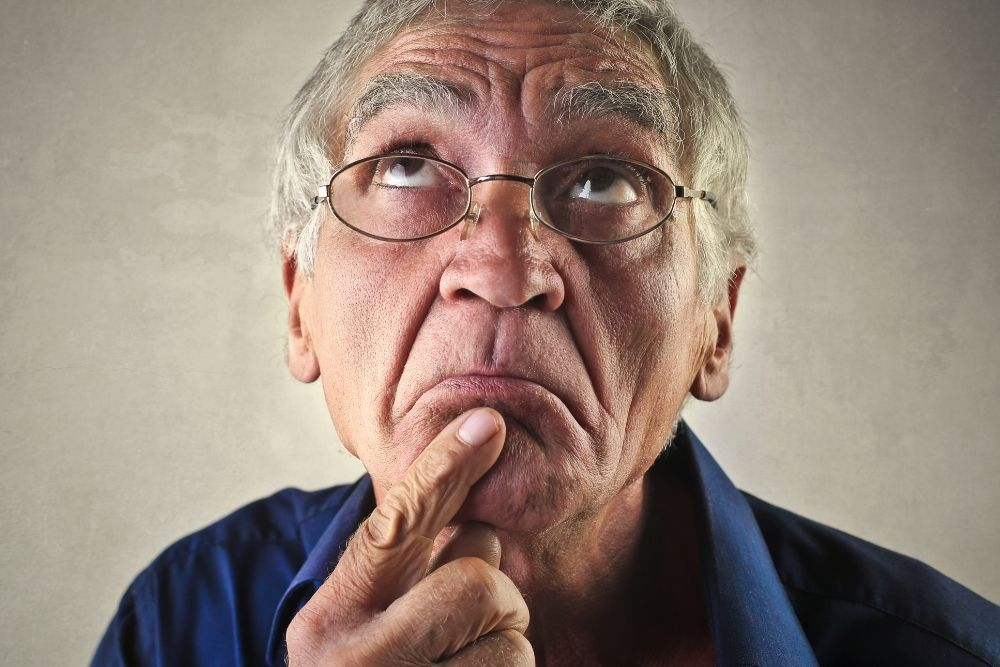 A funny old man is thinking hard on the world's hardest quiz.