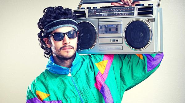 A funny man dressed up in '90s style with typical '90s stereo tape.