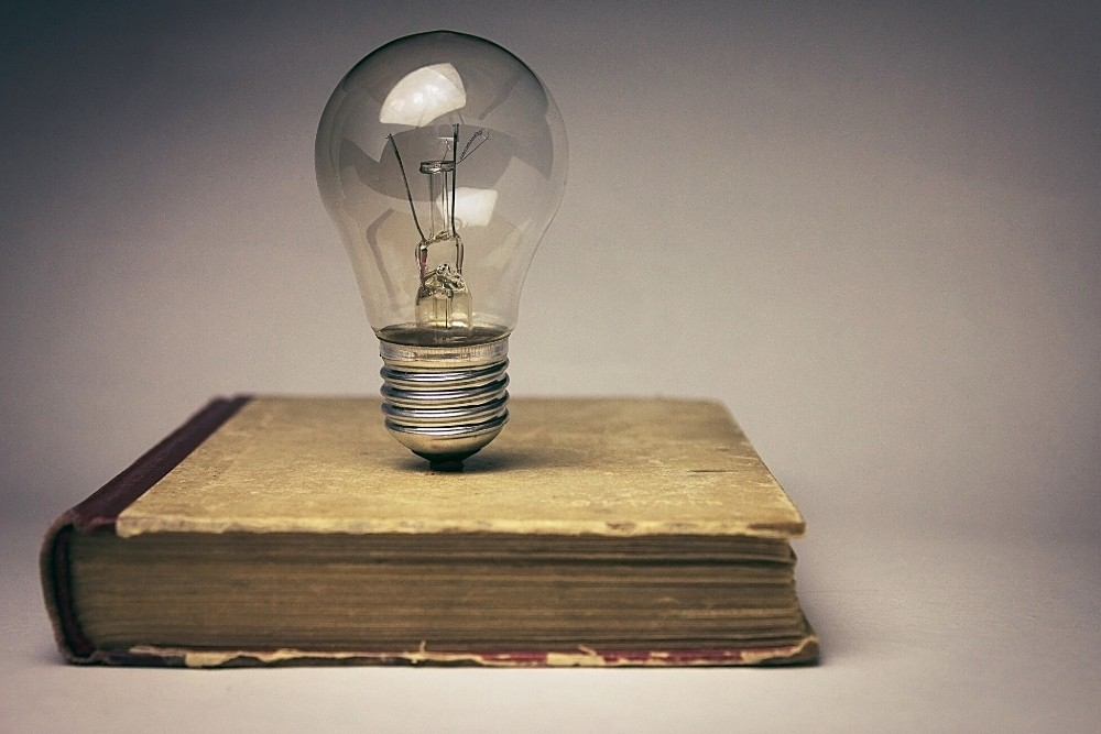 An old general knowledge book with a light bulb above it.