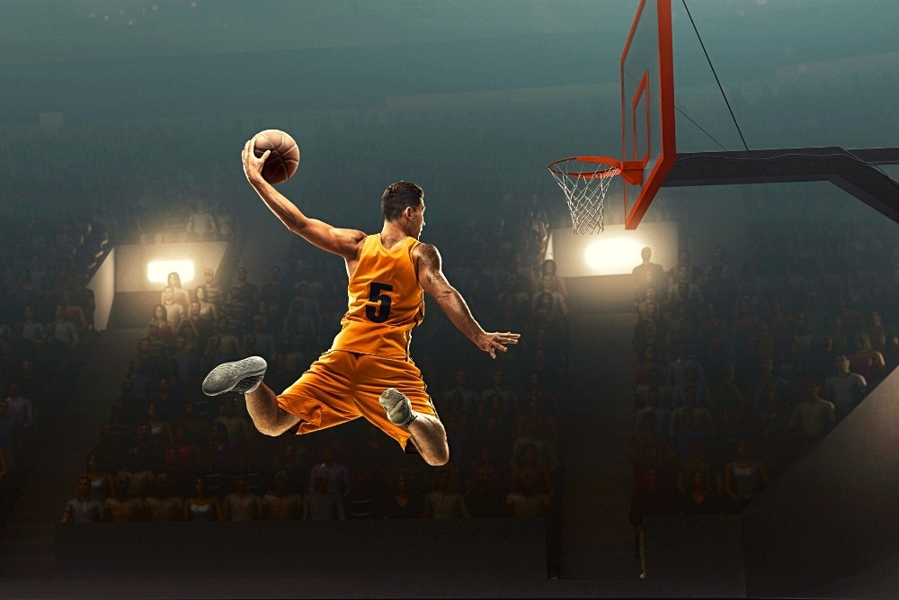 An NBA player in the air with a basketball, trying to dunk it.